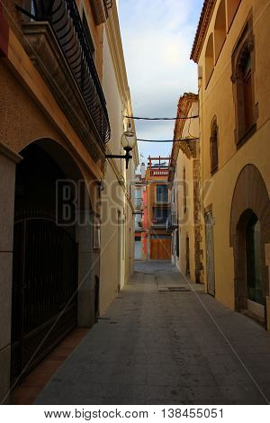 CALELLA, SPAIN - June 27. The narrow streets of the Spanish city, a small, two-storey houses of brown, look beautiful semicircular arch over the window and gate on the opposite side of the street lantern