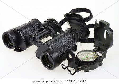 Porro binoculars and military compass on the white background.