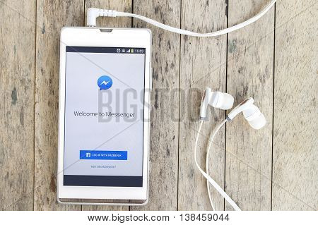 BUNG KAN THAILAND - MARCH 22 2016: smart phone display facebook messenger app with earphones on wood background