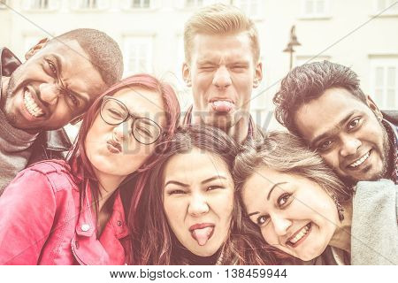 group of young multi-ethnic people taking picture with funny faces looking hilarious