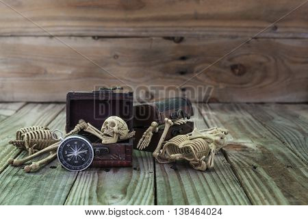 Ghost in the treasure chest with compass on old wood background