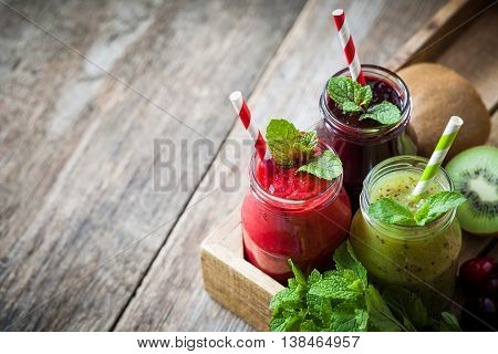 Healthy Smoothie From Kiwi, Raspberries And Blueberries In A Jars With Straws And Mint Leaves In Woo