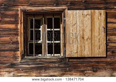 Window of a wooden alpine hut. Rustic background.