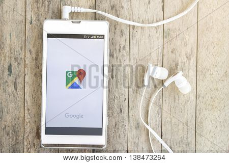 BUNG KAN THAILAND - MARCH 22 2016: smart phone display google map app with earphones on wood background with sunlight