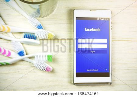 BUNG KAN THAILAND - JANUARY 20 2016: smart phone display facebook app and toothbrush on table smart phone selective focused and color with sunlight