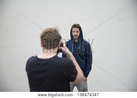 taking pictures of a dude with hoddie in front of a white wall