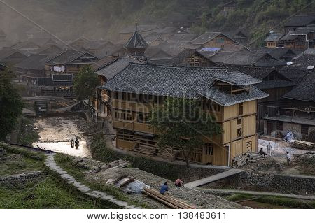 Zhaoxing Dong Village Guizhou Province China - April 8 2010: Sunset in the countryside Dong ethnic minority view of the tiled roofs of wooden huts drum tower and covered bridge evening spring.
