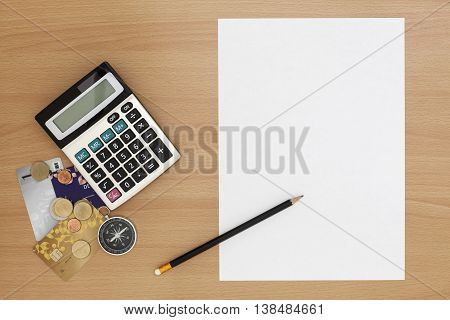 White paper with calculator and pencil on wood backgroundOffice Desk Business concept