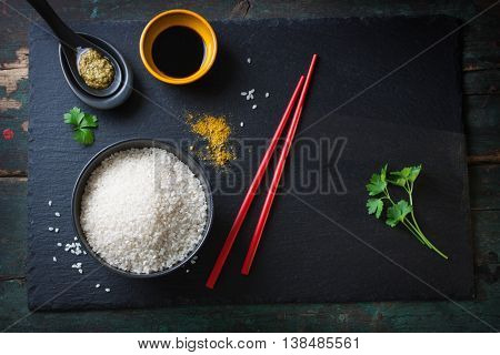 Composition with asian food - rice for sushi spices sauces and chopsticks on a wooden and stone background top view