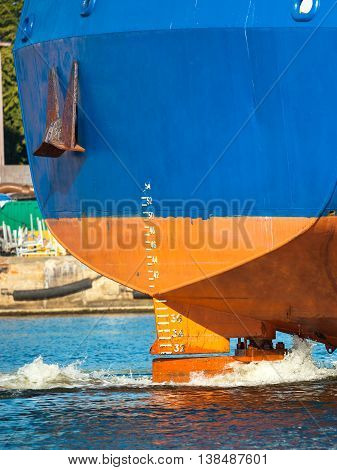 Stern of ship with working screw and rudder.