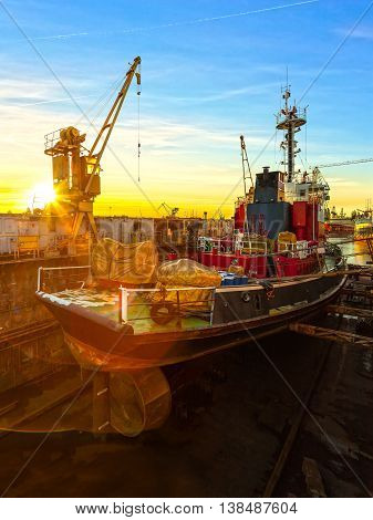 Ship being repaired in dry dock at sunrise in Gdansk Poland.