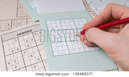 Blank sudoku puzzle and hand with pencil.