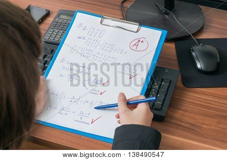 Teacher Is Correcting And Grades Math Exam In School And Gives A