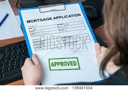 Business woman is holding mortgage application with approved stamp.