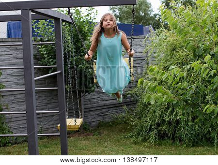 Little Girl In Blue Dress Is Swinging On The Seesaw