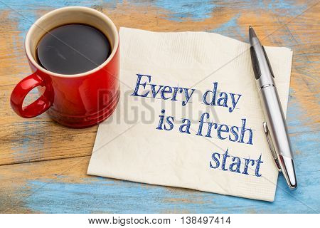 Every day is a fresh start - motivational handwriting on a napkin with a cup of coffee.