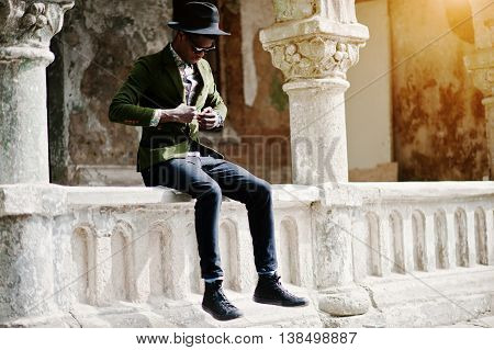 Fashion Portrait Of Black African American Man On Green Velvet Jacket And Black Hat, Sitting On The
