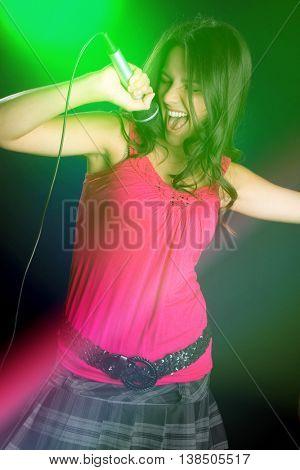 Beautiful karaoke girl singing into microphone