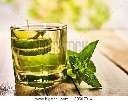 Alcohol drink. On wooden boards is glass with alcohol green transparent drink. Drink number hundred fifty three mohito cocktail with lime. Country outdoor. Light background.
