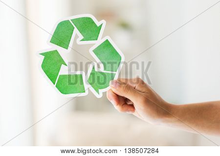 waste recycling, reuse, garbage disposal, environment and ecology concept - close up of hand holding green recycle symbol