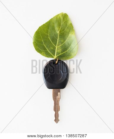 conservation, environment, transport and ecology concept - close up of car key and green leaf trinket