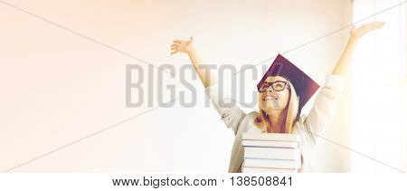 happy student in graduation cap with stack of books