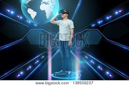 3d technology, virtual reality, cyberspace, global communication and people concept - young man with virtual reality headset or 3d glasses looking at earth hologram over black background and lights