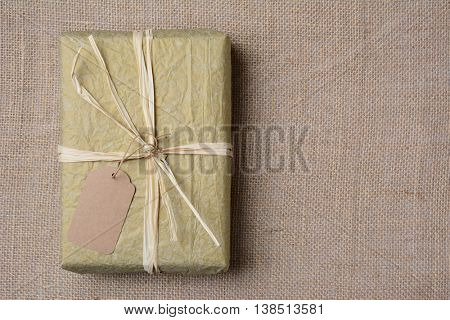 Christmas present wrapped with gold tissue paper, tied with raffia and a blank gift tag. On burlap with copy space.