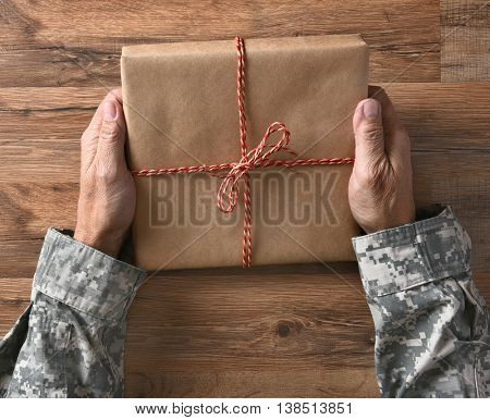 Closeup of a soldiers hands holding a plain wrapped parcel, over a wood background.