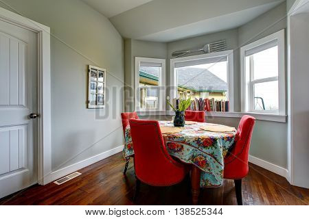Dining Area With Red Soft Chairs And Hardwood Floor.
