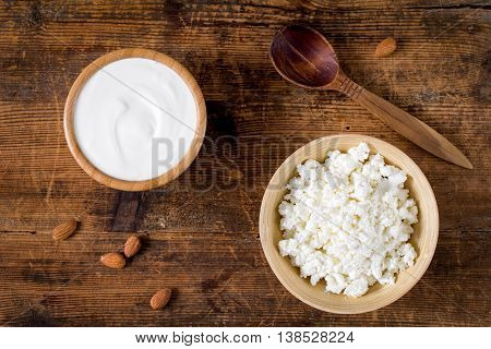 Yogurt and cottage cheese in bowls on wooden background, top view food