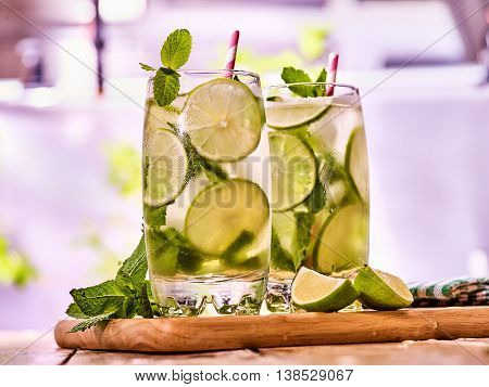 Alcohol cocktail. On wooden boards couple of glasses with alcohol drink and ice cubes. A drink number hundred sixty nine cocktail mohito with mint leaf. Country life. Light background.
