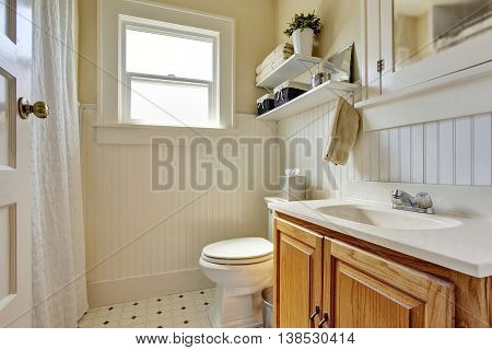 Bathroom Design In Creamy Colors With Brown Wooden Cabinet And Small Window.