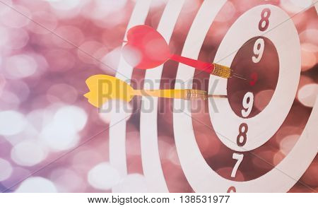target dart with target arrows on the bokeh background and dartboard is the target and goalabstract background to target marketing or target arrow or target business concept .