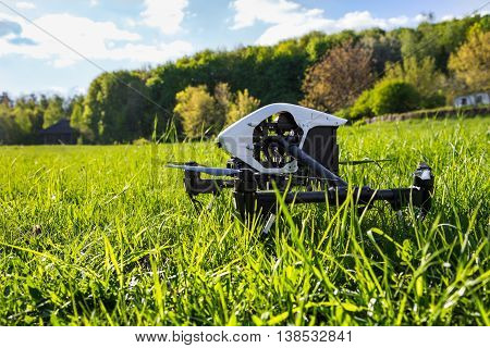 Dron is located in the green grass before takeoff. Copter engine is not running. Low point shooting, close-up.