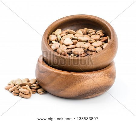 dried fava (broad) bean in a rustic wood bowl isolated on white