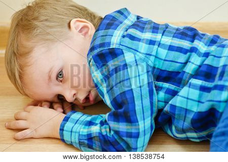 Little Boy Lying On Floor
