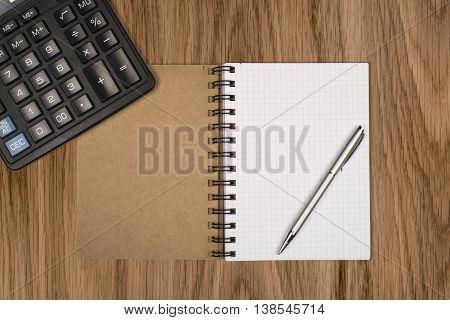 Notebook ballpen and calculator on wooden desk