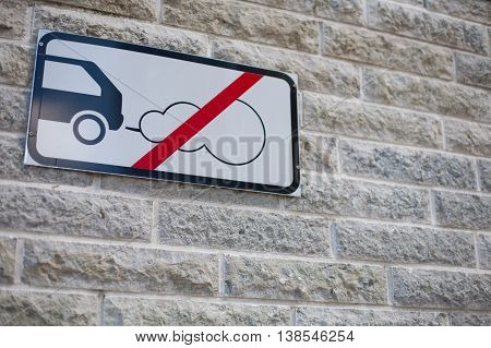 No car carbon dioxide (CO2) emissions allowed sign attached to a stone wall in an environmentally friendly district