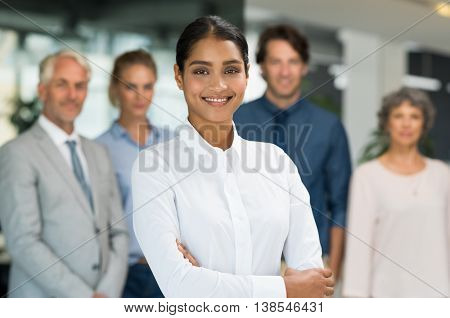 Multiethnic businesswoman standing with her colleagues in background. Portrait of happy smiling business woman looking at camera with team behind. Successful young woman with arms crossed posing.