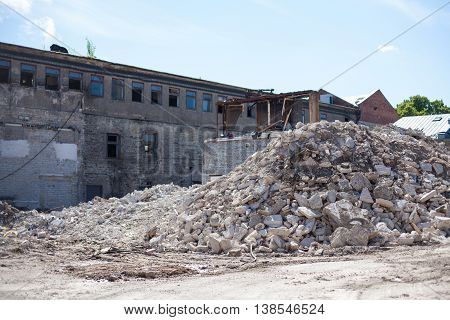 Construction site with an abandoned house and piles of demolition rubble