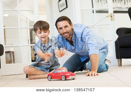 Father with little boy playing with toy car. Smiling father and happy son playing together in living room. Father spending quality time with son at home.