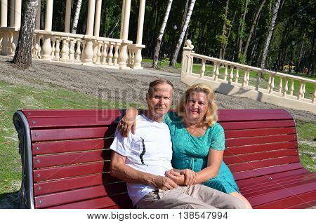 Happy seniors couple portrait, man and woman sittting on a bench in a park