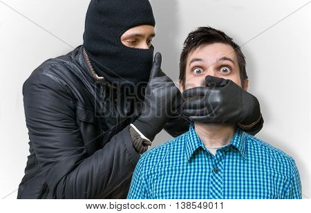 Burglar masked with balaclava and his hostage.