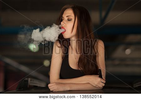 Young beautiful woman smoking ( vaping ) e-cigarette with smoke in car luke