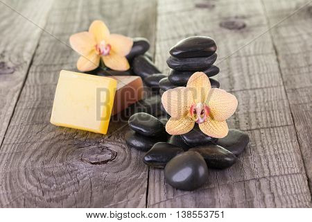 Spa element with soaps, flowers and black stones on weathered wood