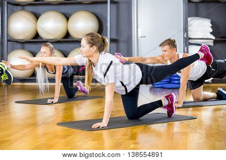 Workout team exercising pilates to strengthen core muscles and balance at the fitness gym.