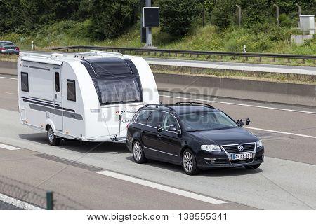 FRANKFURT GERMANY - JULY 12 2016: Volkswagen Passat Estate family car towing a caravan on the highway in Germany
