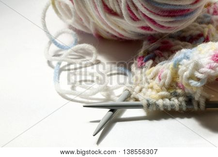 knitting on the spokes  in grey and pink tones