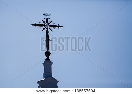 Cross atop a church with sky background